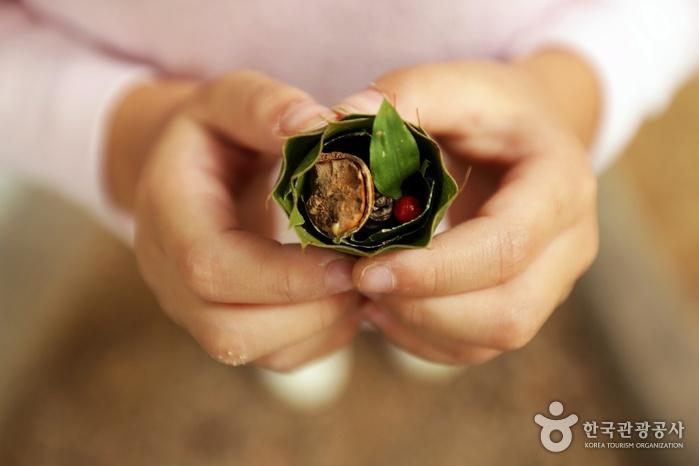 나뭇잎에 열매와 잎을 넣어 김밥모양을 만든 어린이