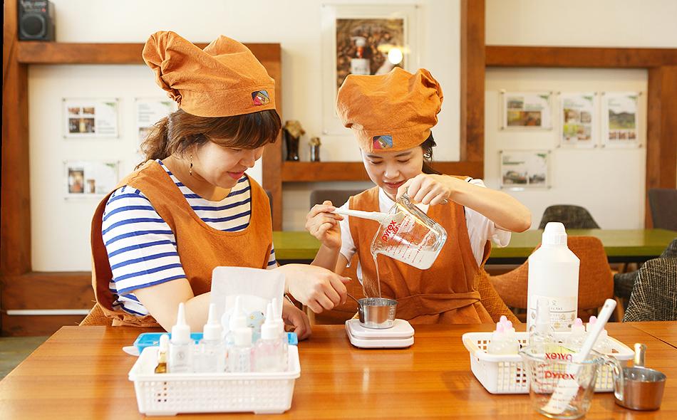 두 여성이 한방 화장품을 직접 만들어 보고있다