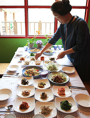 다양한 채소와 나물들이 있는 밥상을 차리고 있다