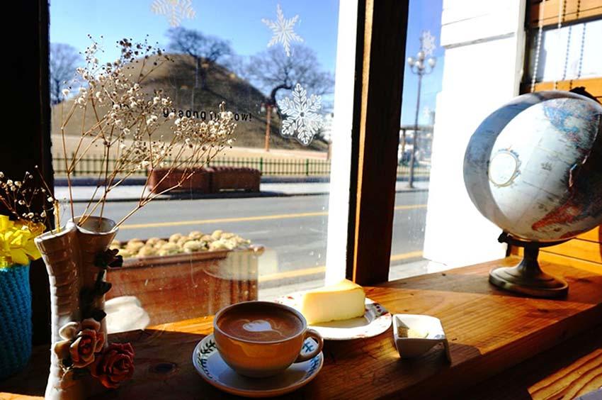 Окно кафе, через которое виднеется могильный курган эпохи Силла