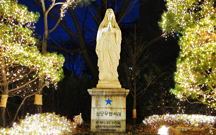 A statue of Mary surrounded by lights at Myeong-dong Cathedral