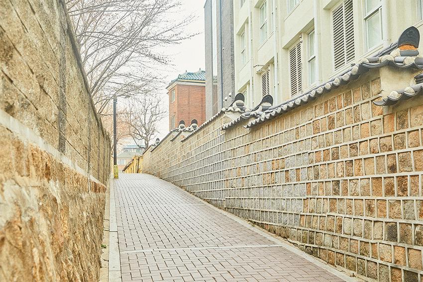 Calle del muro piedra al lado de Wangja Manhwa Bang