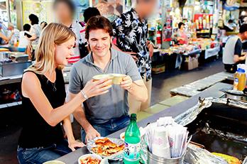 Tourists enjoying snacks at Gwangjang Market