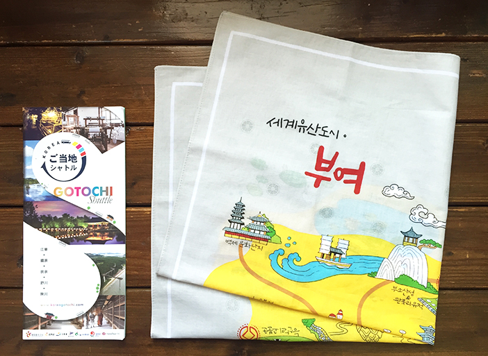 ご当地シャトルパンフレットと参加者にプレゼントされる扶余の観光地が印刷されたハンカチ