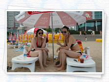 Haeundae Beach in a swimsuit-clad women wearing sunglasses inside a parasol are sitting in a photo