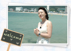 The woman in the photos, smiling at the beach