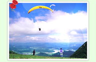 Blue sky and white clouds looking at people who are in the midst of Paragliding