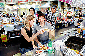 Tourists enjoying snacks at Gwangjang Market