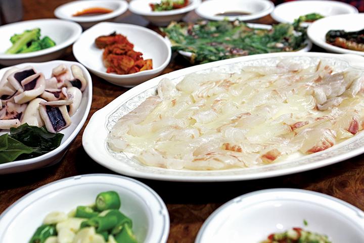 광어회와 밑반찬(오징어, 다시마, 생마늘, 전 등)이 가득한 테이블