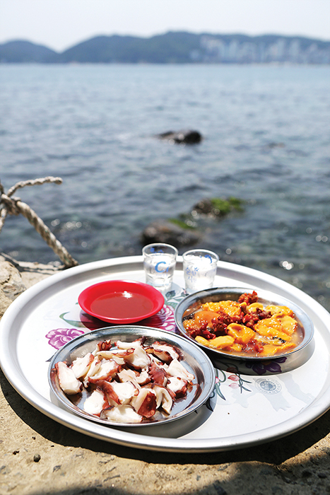 바닷가 바위 위에 놓여있는 음식(소주두잔, 초장, 문어숙회, 멍게)이 담긴 쟁반