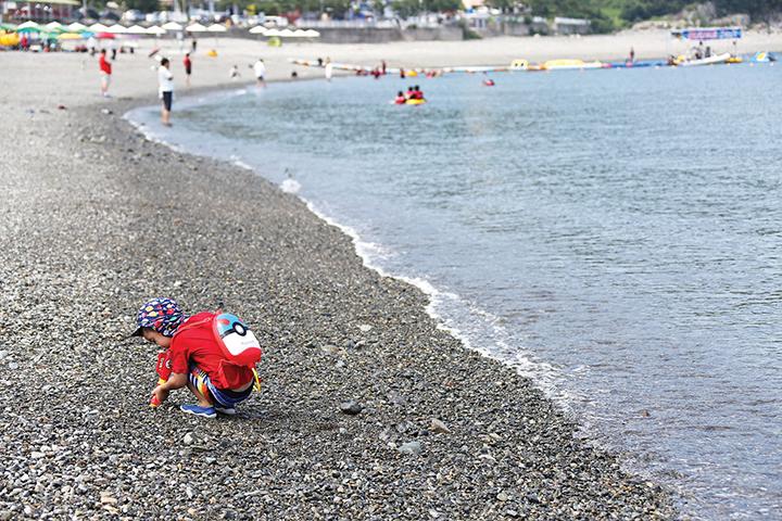 만성리검은모래해변에서 돌맹이를 가지고 노는 어린이