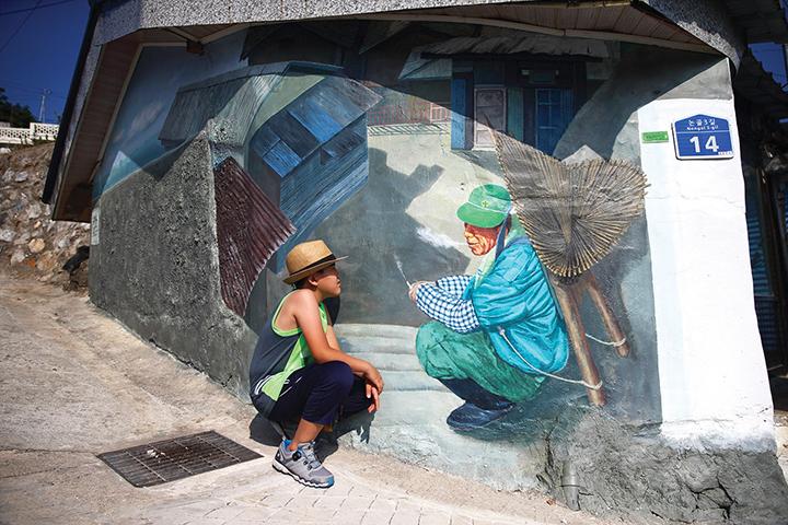 벽화(할아버지가 지게를 지고 앉아서 담배 피우고 계신 그림)를 마주보며 앉은 소년