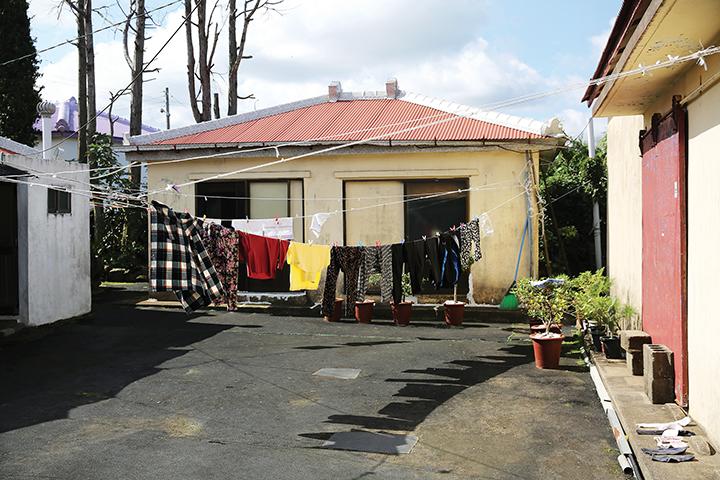 누군가의 집 마당, 마당을 가로 지르는 빨랫줄 위로 여러 벌의 옷이 걸쳐있다