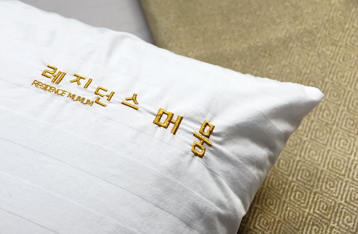 레지던스 머뭄, 침대 위 베개 커버에 수놓여 있는 글자(레지던스 머뭄 Residence Mumum)