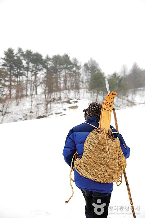 전통 썰매를 챙겨 눈 덮인 언덕을 오르는 눈꽃마을 주민