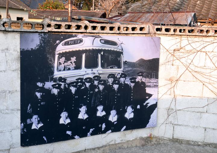 담벼락에 붙어있는 옛날 사진(버스 앞에서 교복을 입은 학생들이 찍은 단체사진)