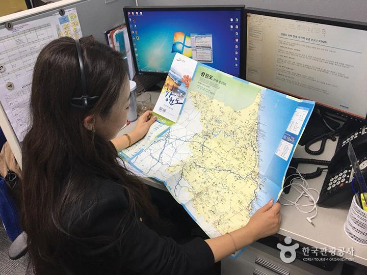 1330 관광통역안내전화 콜센터 직원이 강원도 지도를 보고 있다