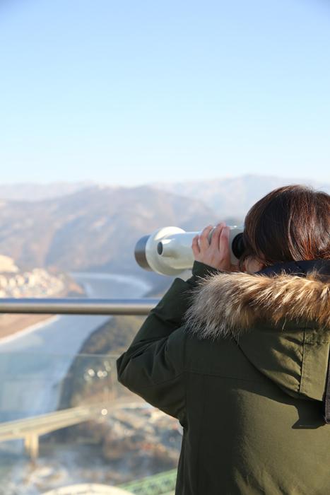 만천하스카이워크에 설치되어 있는 망원경으로 멀리있는 풍경을 바라보는 관광객