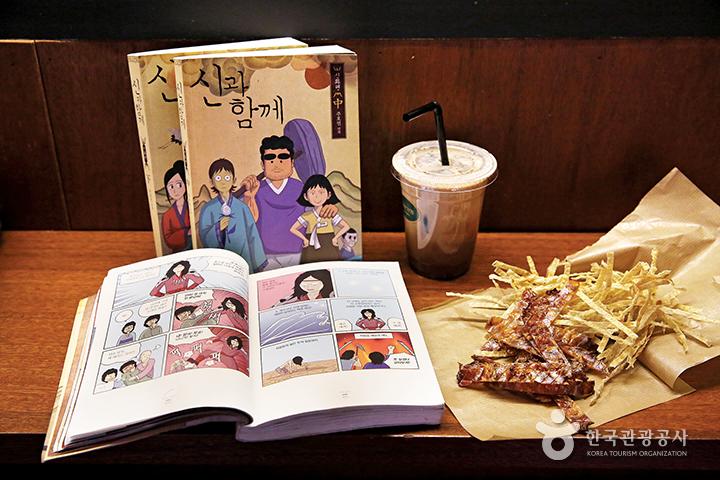 펼쳐진 만화(신과 함께)책과 음료, 쥐포