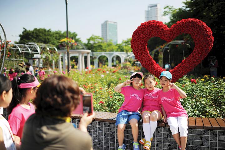하트장미 정원에 앉아 기념사진을 찍는 어린이