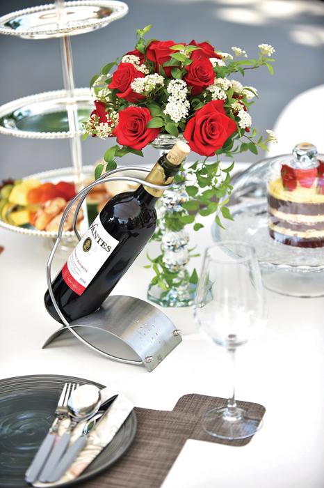 테이블 위에 세팅되어 있는 식기류와 와인, 케잌, 꽃병