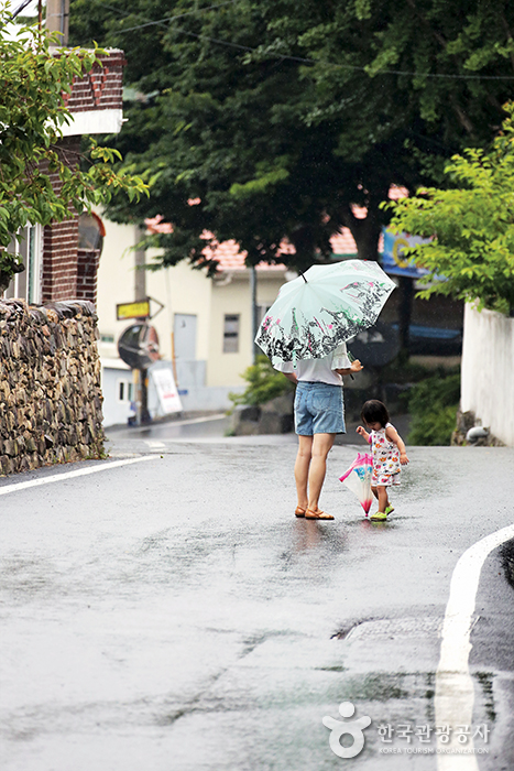 우산을 들고 있는 엄마와 바닥을 쳐다보는 아이